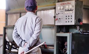 工場で機械を見守る従業員のイメージ写真